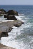 Praia da Azarujinha, beach in Estoril, portugal. Black stone coast with steps to ocean. Praia da Azarujinha, beach in Estoril, portugal Stock Image