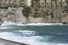 Praia da Azarujinha, beach in Estoril, portugal. hill looks like wall with houses on it and stairs on left side. Praia da Azarujinha, beach in Estoril, portugal Stock Images