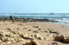 Praia da Oura, Albufeira Portugal - 11/24/2017: Fiskarefiske i Atlanticet Ocean royaltyfria bilder
