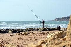 Praia da Oura, Albufeira Portugal - 11/24/2017: Fiskarefiske i Atlanticet Ocean royaltyfria foton