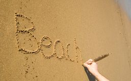 Praia da palavra escrita na areia Fotos de Stock