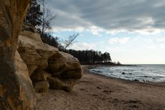 Praia da pedra calcária no mar Báltico com teste padrão bonito da areia e cor vermelha e alaranjada vívida - escritas do turi imagens de stock royalty free