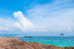 Praia da rocha com água claro e o barco fotos de stock royalty free