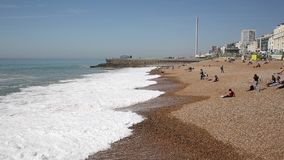 Praia de Brigghton no tempo bonito com as ondas que deixam de funcionar dentro e os povos e o cais video estoque