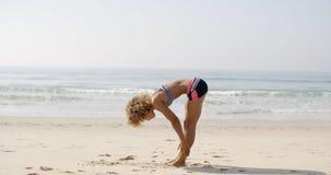 Praia de Doing Exercise On do atleta fêmea Fotos de Stock Royalty Free