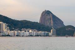 Praia de Leme e de Copacabana em Rio de janeiro que negligencia o naco de açúcar no por do sol fotos de stock royalty free