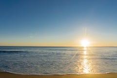 Praia de Papamoa, outlok ao fulgor dourado do horizonte em sunris Foto de Stock