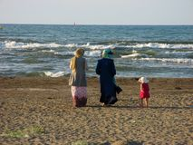 Praia de passeio do hijab muçulmano das mulheres Mulheres muçulmanas no hijab que andam na praia do mar Cáspio em Irã, Anzali imagem de stock