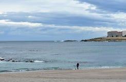 Praia de Riazor com a mulher que anda um cão Dia chuvoso, La Coruna, Espanha imagens de stock