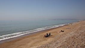 Praia de Seaford com os povos nos deckchairs, no banho de sol e nas ondas Sussex do leste Reino Unido filme