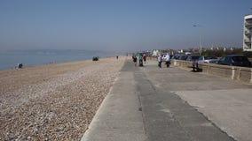 Praia de Seaford e passeio Sussex do leste com os visitantes que andam na luz do sol vídeos de arquivo