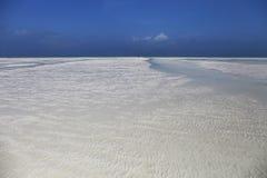 Praia de surpresa com a areia branca em Zanzibar, Tanzânia imagens de stock royalty free