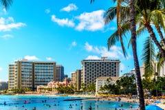 Praia de Waikiki, com seus muitos recursos sob o céu azul e a areia branca Imagens de Stock