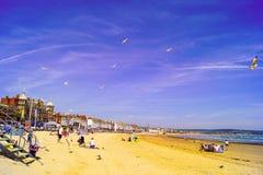 Praia de Weymouth ocupada com as famílias que apreciam seu feriado fotografia de stock