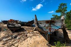 Praia de Zanzibar com os barcos e lixo abandonados velhos fotografia de stock