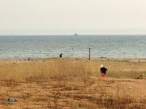 Praia do mar, povos de passeio e submarino de vinda no horizonte foto de stock