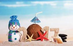 Praia do Natal com a inscrição 2017, o boneco de neve e o coco Fotografia de Stock