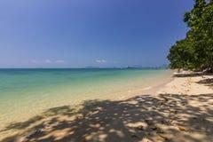 Praia do oceano e sombra azuis da palma na água na ilha phangan fotos de stock royalty free