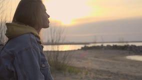 Praia do outono do por do sol e menina triste que sentam-se na árvore filme