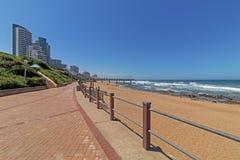 A praia do passeio balança a skyline litoral azul da cidade das ondas de oceano imagem de stock
