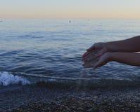 A praia do tempo da vida da mão o oceano descalço da beleza dos povos do curso da natureza da palma da areia relaxa a areia human Foto de Stock Royalty Free