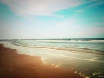 Praia e céu nebuloso Imagens de Stock