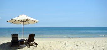 Praia e cadeira Fotos de Stock Royalty Free