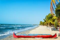 Praia e canoa vermelha Fotografia de Stock Royalty Free