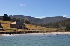 Praia e construção velha no parque nacional da ilha de Maria, Tasmânia, Austrália imagem de stock