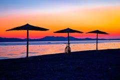 Praia e parasóis na opinião colorida do por do sol foto de stock