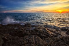 Praia e rocha do mar no tempo do por do sol Imagens de Stock Royalty Free