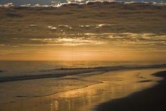 Praia em bancos exteriores no por do sol fotografia de stock