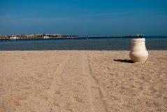Praia ensolarada da areia com jarro e duas trilhas Potenciômetro cerâmico na areia na praia Oceano azul e jarro branco na praia Fotografia de Stock Royalty Free