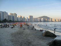 Praia Grande Beach Brazil. Rocks at the first plane, the tourists and the buildings at the shore of the beach of Praia Grande, Sao Paulo state, Brazil Stock Images