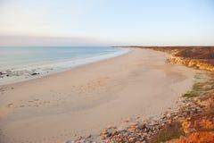 Praia infinita com formação de rocha vermelha imagens de stock royalty free