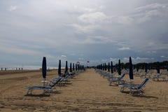 Praia Itália de Bibione com o céu azul e os guarda-sóis claros Fotos de Stock Royalty Free