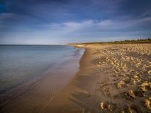 Praia longa, vazia e limpa de Stogi da areia no por do sol perto de Gdansk, Polônia com o céu azul dramático imagens de stock