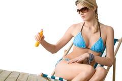 Praia - a mulher nova no biquini aplica a loção do suntan fotografia de stock