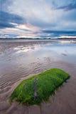Praia na maré baixa durante um por do sol nebuloso Imagem de Stock