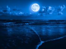 Praia na meia-noite com uma Lua cheia Imagem de Stock