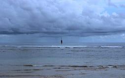Praia nebulosa com a uma silhueta do homem fotografia de stock royalty free