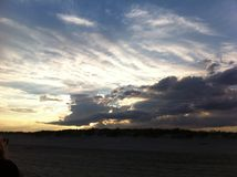 Praia no crepúsculo com nuvens brilhantes foto de stock royalty free