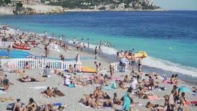 A praia pública aglomerada no litoral, muitos povos expõe ao sol bronzear-se ou espirrar na água vídeos de arquivo