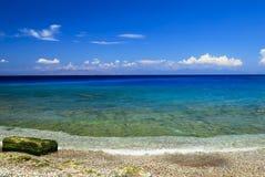Praia pitoresca do verão, rochas na linha da ressaca em um mar bonito no Rodes, Grécia, curso, recreação, conceito das férias Sea fotos de stock