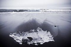 Praia preta da areia com gelo Foto de Stock