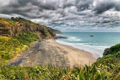 Praia preta vazia bonita da areia na baía maori perto da praia de Muriwai, Nova Zelândia fotografia de stock royalty free