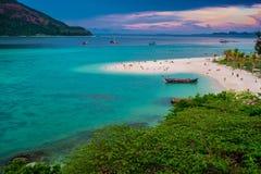 : A praia que estende no mar que olha para fora para ver a ilha e o céu azul lá é muitos barcos que flutuam no SE verde esmeralda fotos de stock royalty free