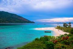 A praia que estende no mar que olha para fora para ver a ilha e o c?u azul l? ? muitos barcos que flutuam no verde esmeralda fotos de stock royalty free