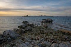A praia rochosa bonita com o céu colorido na ilha de Harapan mas infelizmente mantido mal e tem lotes do desperdício plástico fotografia de stock