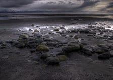 Praia rochosa com nuvem de tempestade imagens de stock royalty free